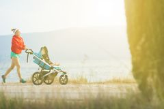 Running mother with baby stroller enjoying sunset landscape Royalty Free Stock Image