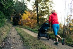 Running mother with stroller enjoying motherhood at autumn sunse. Running mother with child in stroller enjoying motherhood at autumn sunset and mountains Royalty Free Stock Photo