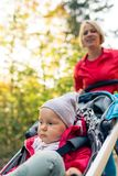 Running mother with stroller enjoying motherhood in autumn. Running mother with contemplative child in stroller enjoying motherhood at autumn sunset and forest Stock Photos