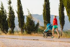 Running mother with stroller enjoying motherhood at sunset lands Stock Photo