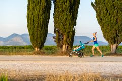 Running mother with stroller enjoying motherhood at sunset lands. Running mother with child in stroller enjoying motherhood at sunset and mountains landscape Royalty Free Stock Photo