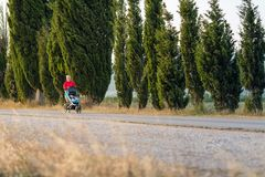 Running mother with stroller enjoying motherhood at sunset lands Stock Photos