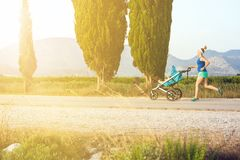 Running mother with stroller enjoying motherhood at sunset lands. Running mother with child in stroller enjoying motherhood at sunset and mountains landscape stock photos