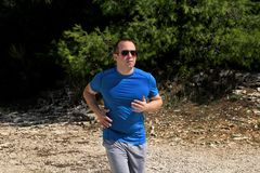 Running muscular man athlete runner training outdoor in forest. Running runner sportsmen wearing sportswear in cross country. Royalty Free Stock Photos