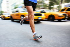 Running in New York City - man city runner. Jogging in street of Manhattan with yellow taxi caps cars and traffic. Urban lifestyle image of male jogger training stock images