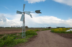 Running old metal windmill in rural landscape Royalty Free Stock Photos