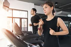 Free Running On Treadmills, Active Young Woman And Man Running On Treadmill In Gym Stock Photography - 123660762