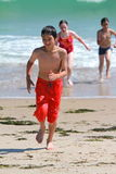 Running out of the ocean. A multi ethnic young teen laughs  while running out of the ocean Stock Photo