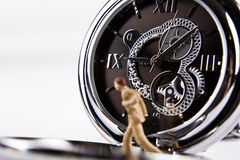 Running out of time. Miniature businessman with watch in background Royalty Free Stock Photo