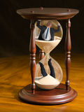 Running out of time hour glass with man inside. A very dramatically lit photo of a large hour glass with a man inside on a wooden table representing time running royalty free stock photos