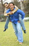 Running Outdoor. A man piggy back his girlfriend. fun playing outdoor on summer day Stock Images