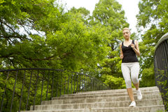 Running over steps. Scenic view of young woman running over steps in park with leafy green trees in background stock photography