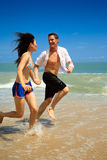 Running on a paradise beach. Couple running on beach holding hands smiling Royalty Free Stock Image