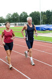 Running Pensioners. Senior couple running together on a track in a stadium Royalty Free Stock Photography