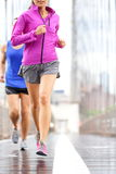 Running people - couple jogging in New York City. Running people - couple jogging and training for marathon. Runners in rain outside. Asian women and Caucasian royalty free stock photos