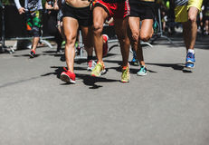 Running people on crossfit competition, feet on the road close up photo Stock Images