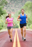 Running people - two smiling runners jogging stock image