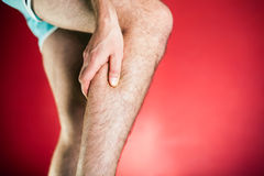 Running physical injury, leg pain. Running physical injury, leg calf pain. Runner sore body after exercising, red background Royalty Free Stock Photos