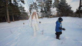 Running and playing in the snow. Family of mother and child play games during winter holiday stock video footage