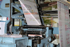 Running the press. GREYMOUTH, NEW ZEALAND, MAY 22, 2015:  Newsprint speeds through the folder while printing a newspaper on May 22, 2015 in Greymouth, New Royalty Free Stock Photos