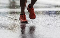 Running in the rain. Closeup of legs in sports shoes running in the rain royalty free stock photos