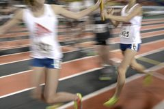 Running a Relay Race on Track Handing Off Baton. Runner running a relay race around a track with lines handing off baton Stock Photo