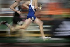 Running a Relay Race on Tract Holding Baton Royalty Free Stock Images