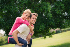 Running ridtur på axlarna för unga par i stadspark royaltyfri foto