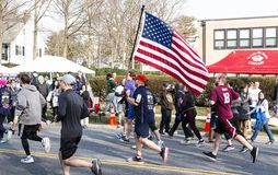 Running road 5K race carrying American Flag royalty free stock images