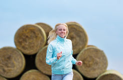 The running romantic girl outdoors against hay stack Stock Image