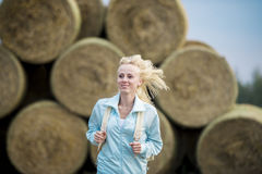 The running romantic girl outdoors against hay stack Royalty Free Stock Image