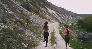 Running on the roof top at nature two ladies with a perfect fit bodies , in a summer day beside of big mountains