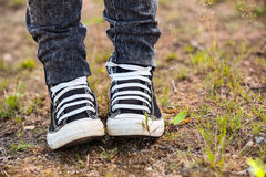 Running rubber shoes are on the legs, person standing on earth Royalty Free Stock Photos