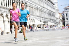 Running runner couple jogging in Venice. Two runners, Asian women and Caucasian men training on travel vacation as tourists on Piazza San Marco Square, Venice royalty free stock image