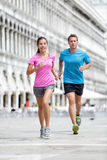 Running runner couple jogging in Venice. Two runners, Asian women and Caucasian men training on travel vacation as tourists on Piazza San Marco Square, Venice stock photography