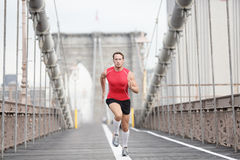Running runner man. Sprinting at speed. Male athlete training alone in full body wearing red compression top and socks during run on Brooklyn Bridge, New York Stock Photos
