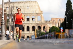 Running runner man by Colosseum, Rome, Italy. Male athlete training for marathon jogging in city of Rome in front of Coliseum in full body length. Fit male Stock Images