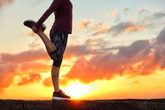 Running runner stretching leg preparing for run. Running runner woman stretching leg muscle preparing for sunset trail run in outdoor summer nature. Female royalty free stock image