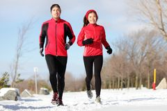 Running. Runners exercising in winter. Male and female runner training for marathon. Healthy lifestyle image with interracial active couple jogging in snow Stock Photos