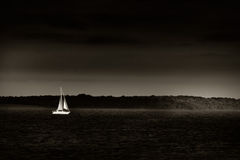 Running or sailing away. Small sailboat getting away from a rising storm. Sepia-toned for contrast and mood Stock Image