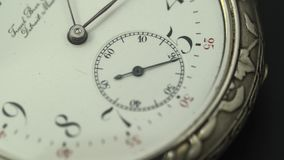Running second hand on an old pocket watch with a white dial. Close up. Running second hand on an old vintage pocket watch with a white dial. Close up stock footage