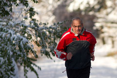 Running senior in snow. Senior running in the snow Royalty Free Stock Images