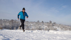 Running senior in the snow. Senior athlete running in the snow Royalty Free Stock Photo