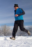 Running senior in the snow. Senior athlete running in the snow Stock Photos