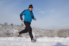 Running senior in the snow. Senior athlete running in the snow Stock Image
