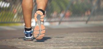 Running shoe closeup of man running on road stock photography