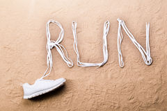 Running shoe and run sign made of shoelaces, sand Stock Image