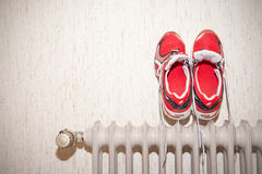 Running Shoes. Indoor shot of a pair of wet and dirty running shoes drying on a radiator Royalty Free Stock Photos