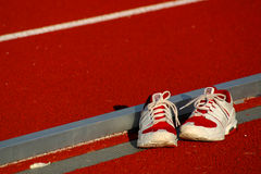 Running shoes. A pair of running shoes sit beside a track Royalty Free Stock Photography