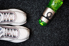Running shoes and bottle of water royalty free stock photo